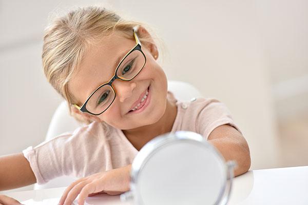 child looking at eyeglasses
