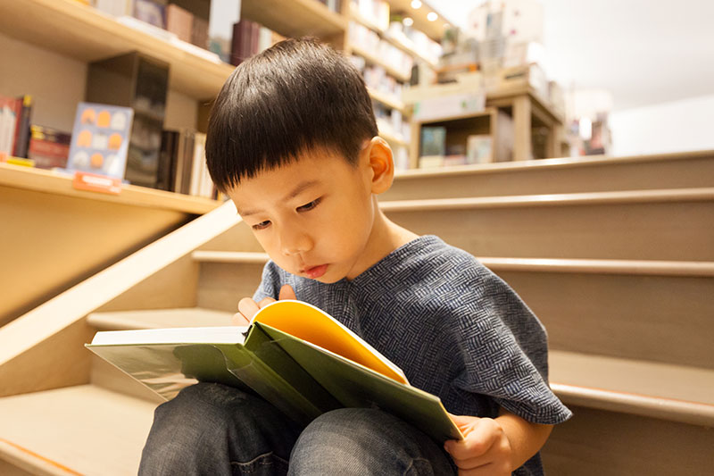young boy reading looking closely at book