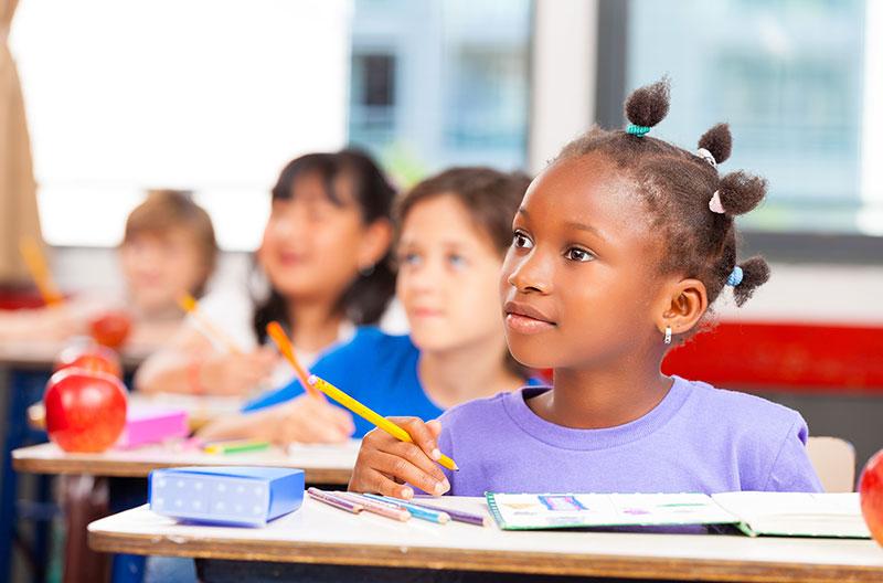 Young girl in school listening